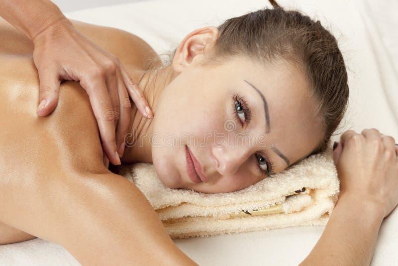 Mulher relaxado que recebe uma massagem do ombro imagens de stock royalty free