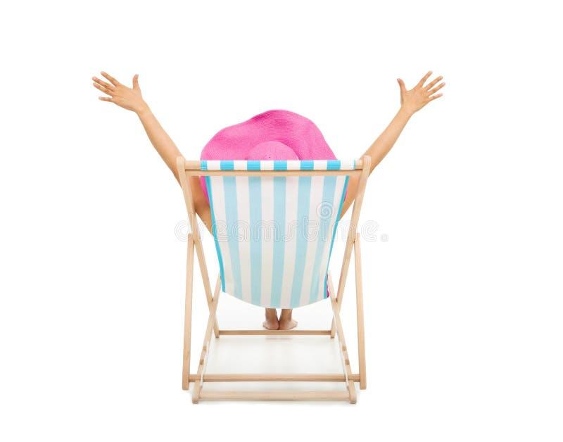 Mulher relaxado que senta-se em cadeiras de praia imagem de stock royalty free