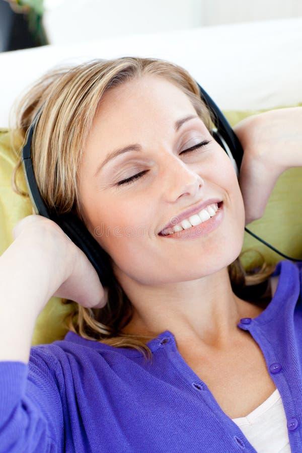 A mulher Relaxed escuta a música com olhos fechados imagens de stock