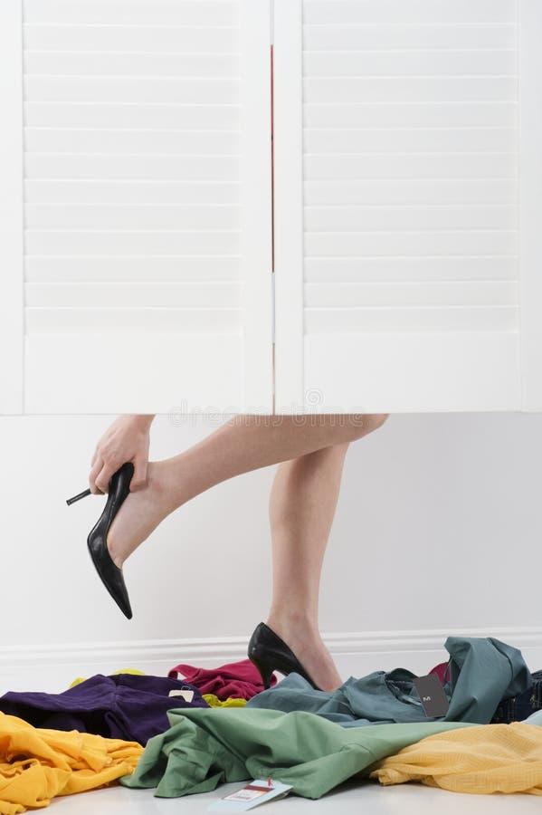 A mulher remove os saltos altos em sala apropriada foto de stock