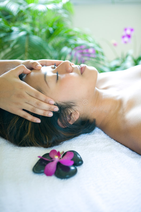 Mulher restful ao estar na massagem principal imagem de stock