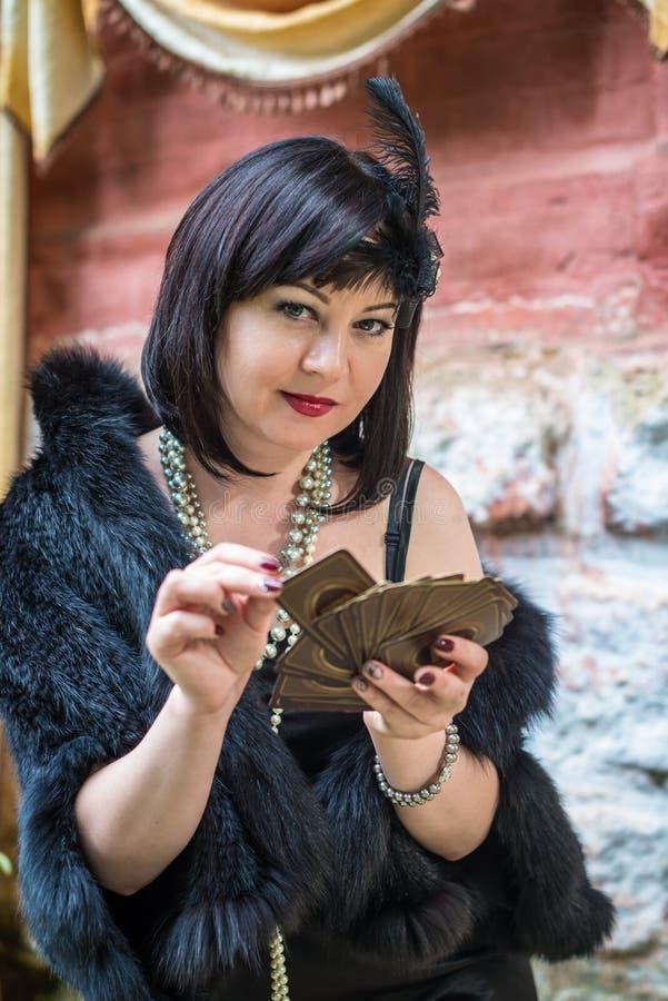 Mulher retro bonita que guarda cartões de jogo foto de stock royalty free