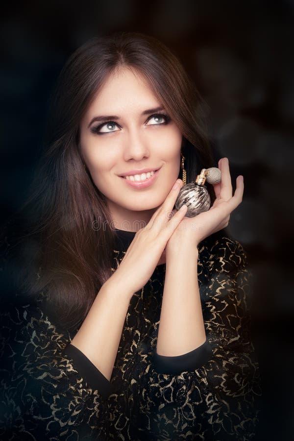 Mulher retro do encanto que guarda a garrafa de perfume do vintage imagens de stock royalty free