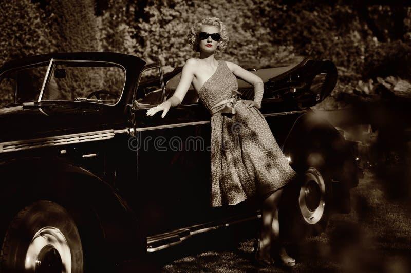 Mulher retro que está perto do convertible foto de stock royalty free