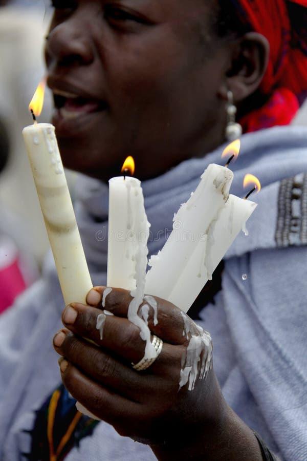 A mulher reza com as velas ardentes nas mãos fotografia de stock royalty free