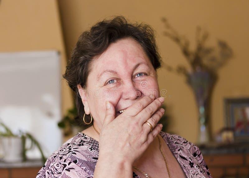A mulher ri, cobrindo sua boca com sua mão fotos de stock royalty free