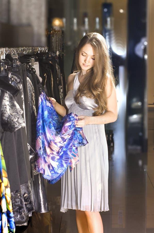 A mulher rica escolhe um vestido em um boutique fotos de stock