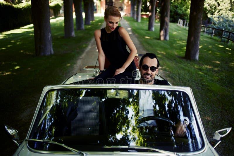 A mulher rica lindo sentir tão contente quando eles equitação no cabriolet com o certo homem moreno considerável imagem de stock