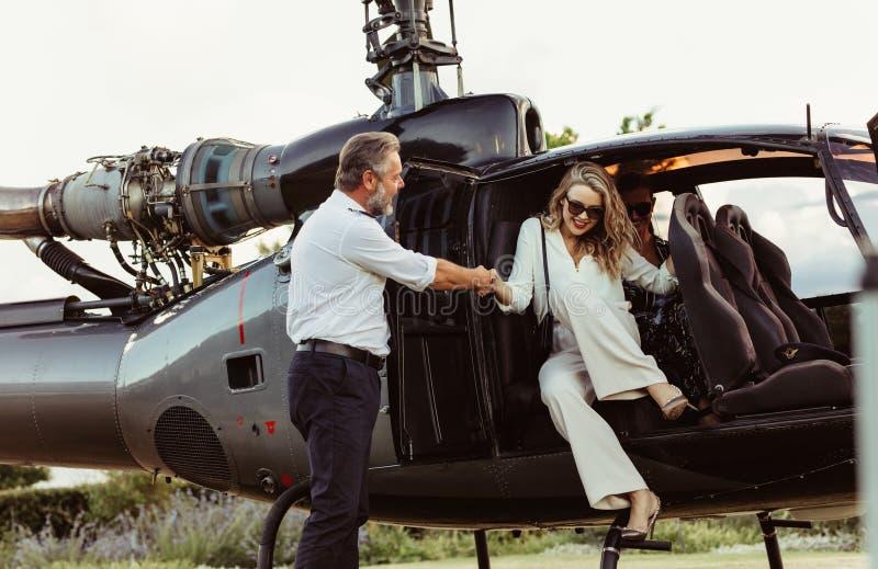 Mulher rica que viaja por seu helicóptero fotografia de stock