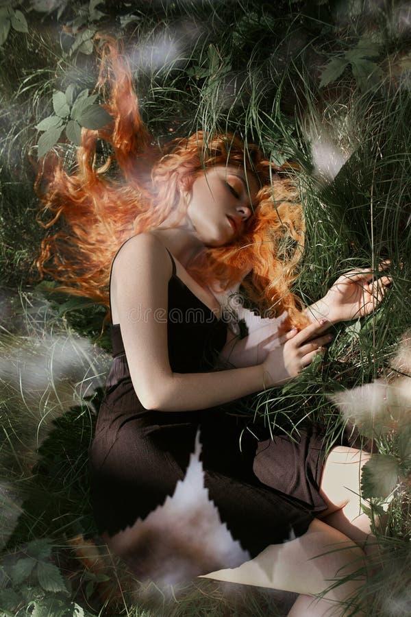 Mulher romântica com o cabelo vermelho que encontra-se na grama nas madeiras Uma menina em sonos pretos claros e em sonhos de um  fotografia de stock