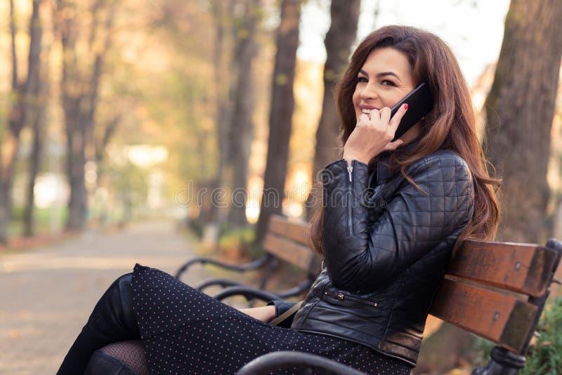 Mulher romântica no parque que fala no telefone imagem de stock