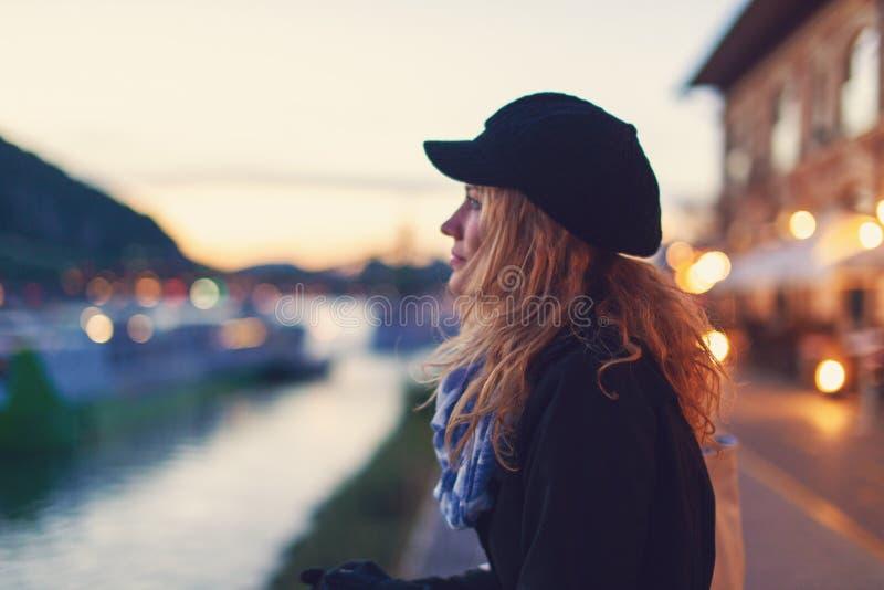 Mulher romântica nova que sonha acordado na noite da cidade fotos de stock