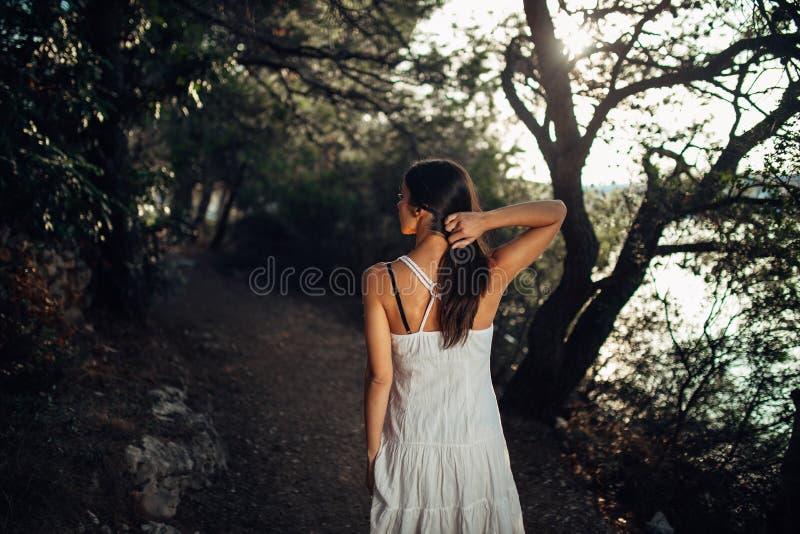 Mulher romântica que aprecia a caminhada na natureza em uma manhã ensolarada A fêmea despreocupada consciente no esforço do senti fotos de stock royalty free