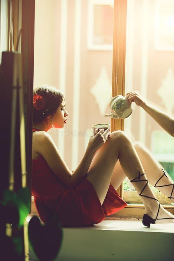 Mulher romântica que pensa sobre o futuro mulher no chá bebendo do vestido vermelho do copo fotografia de stock