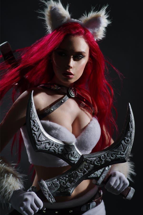 Mulher ruiva sexy em fantasia de gato guerreiro com espadas imagens de stock royalty free