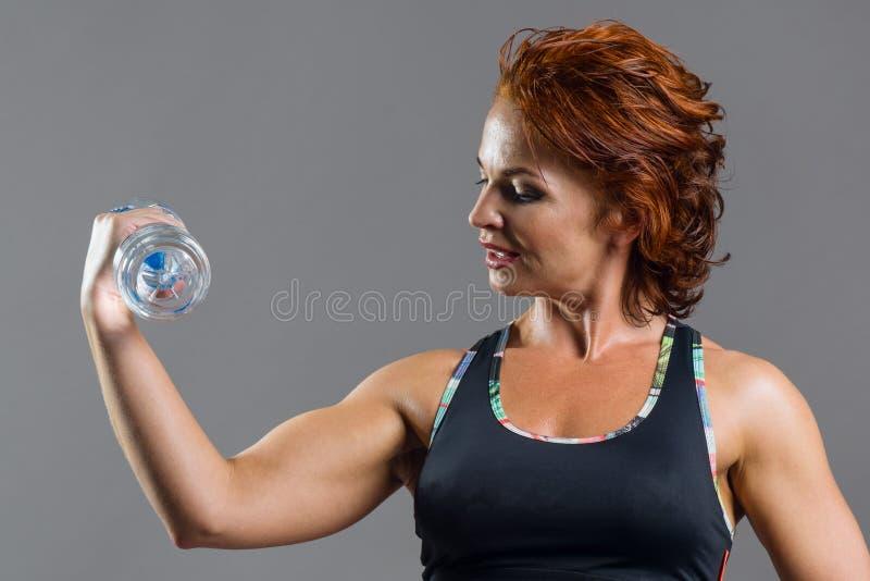 Mulher ruivo da aptidão atlética adulta nos esportes uniformes com uma garrafa da água foto de stock