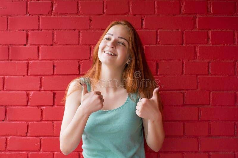 Mulher ruivo de sorriso feliz que mostra os polegares acima foto de stock royalty free