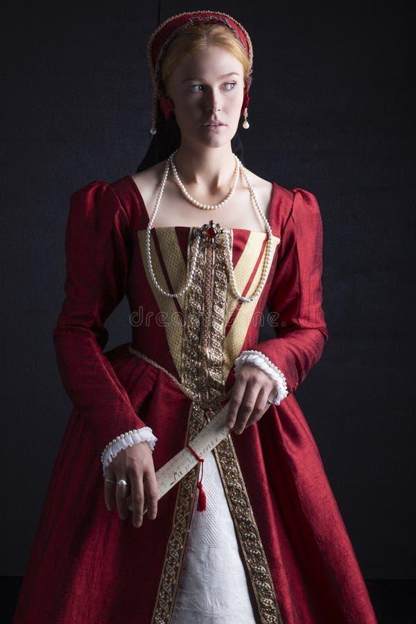 Mulher ruivo de Tudor no vestido vermelho foto de stock royalty free