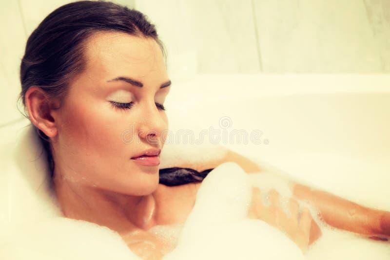A mulher ruivo despida bonita nova toma o banho de espuma imagem de stock