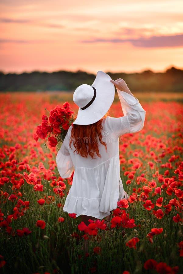Mulher ruivo nos suportes brancos do chapéu no campo florescido de papoilas vermelhas com o o seu de volta à câmera imagens de stock royalty free