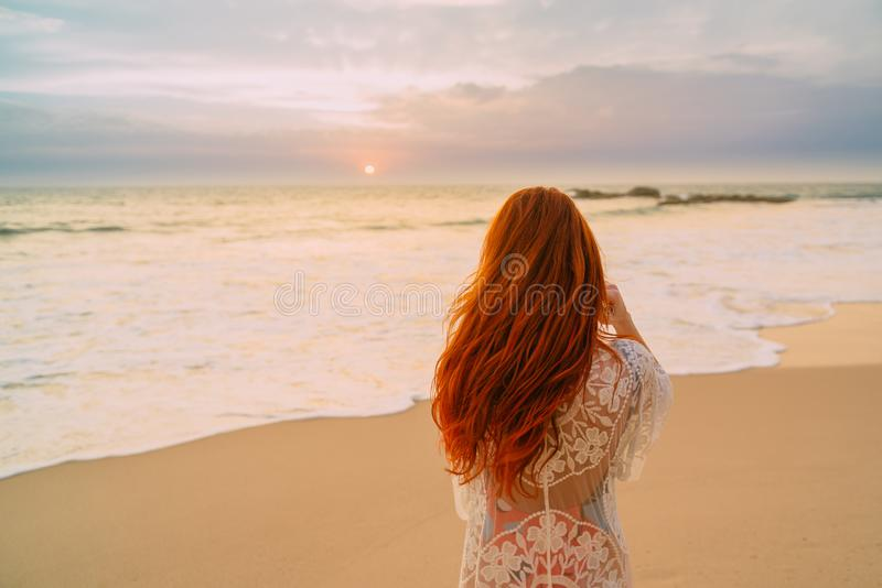 Mulher ruivo nova com cabelo no oceano, vista traseira do voo fotos de stock royalty free