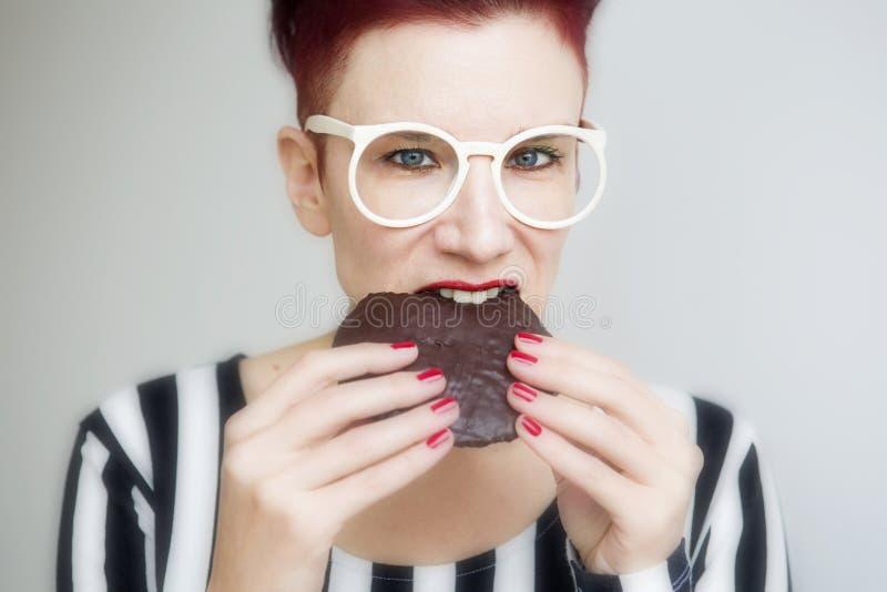 Mulher ruivo que come uma cookie grande do chocolate foto de stock