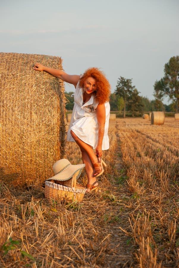 Mulher ruivo que levanta no campo perto de uma pilha do feno foto de stock