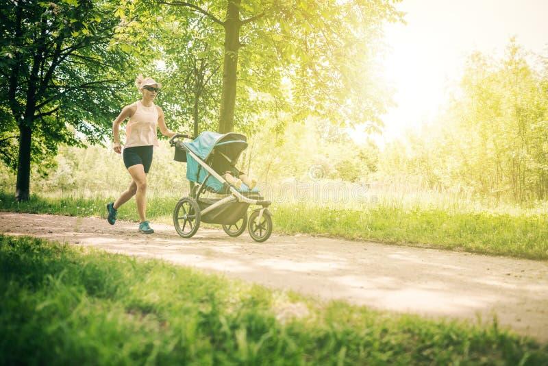 Mulher running com o passeante de bebê que aprecia o verão no parque imagens de stock royalty free