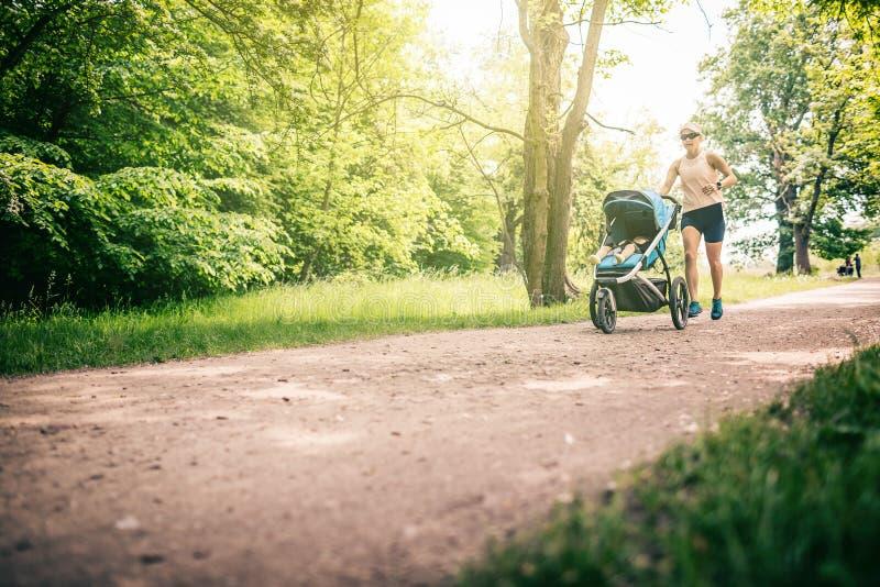 Mulher running com o passeante de bebê que aprecia o verão no parque fotos de stock