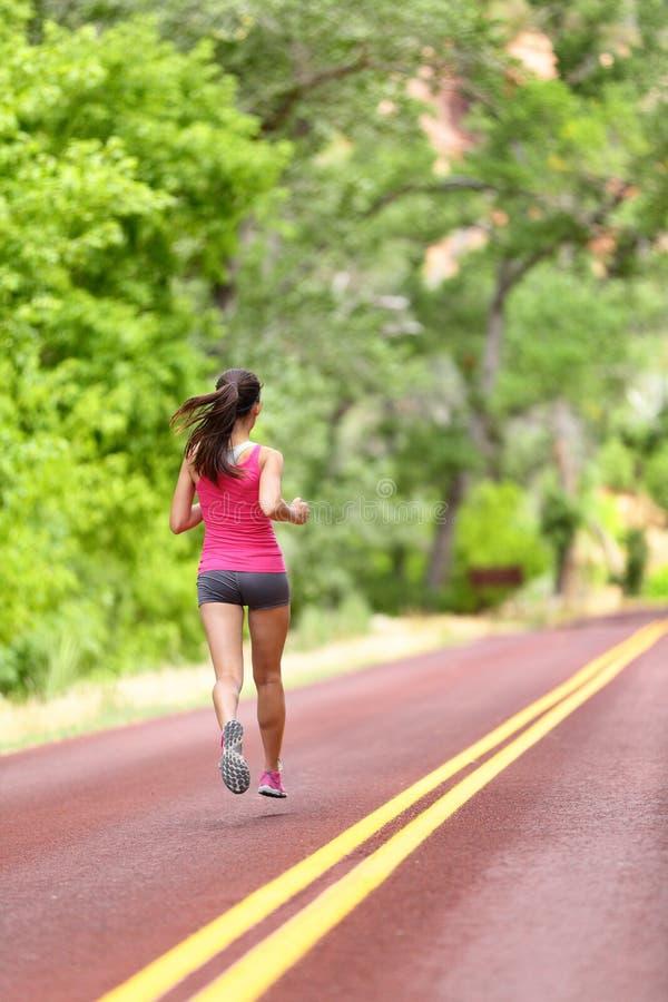 Mulher running - treinamento fêmea do corredor na estrada imagens de stock royalty free