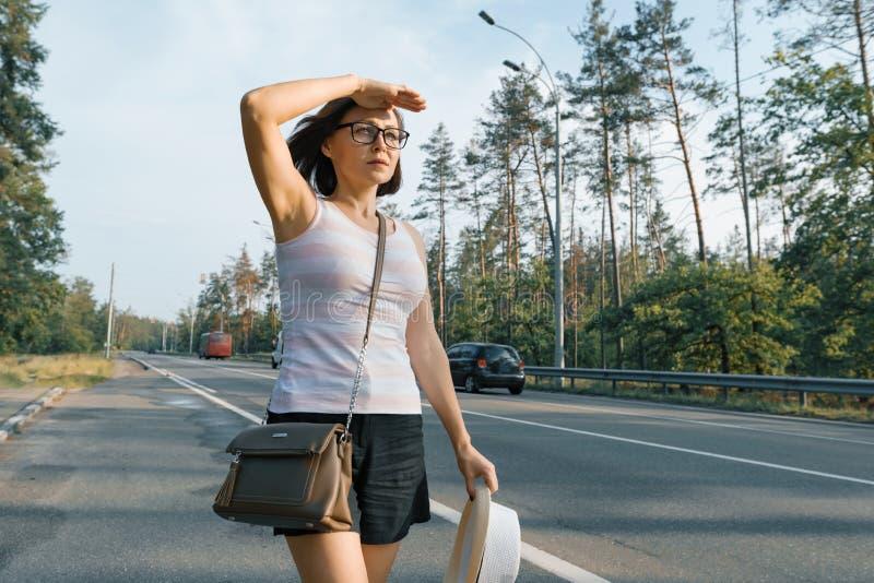 Mulher séria adulta que olha a estrada, vista fêmea para fora na distância com mão a seus olhos fotografia de stock