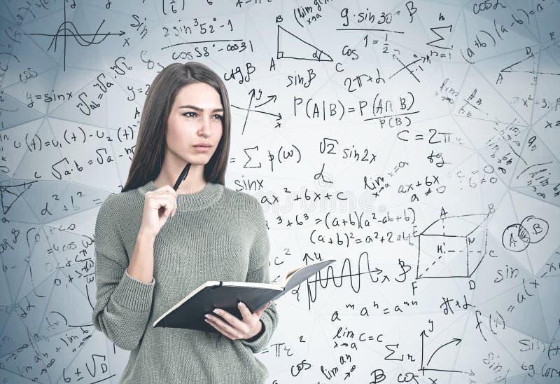 Mulher séria com caderno, fórmula da matemática imagens de stock