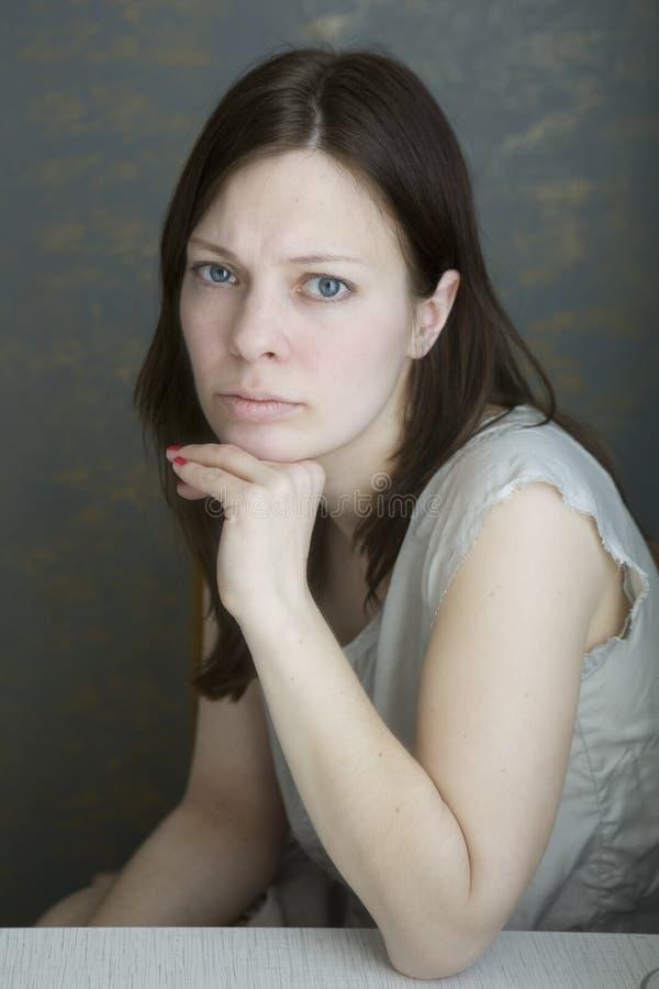 Mulher séria com os olhos azuis que sentam-se na tabela fotografia de stock royalty free