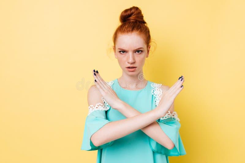 Mulher séria do gengibre no gesto da parada da exibição do vestido foto de stock