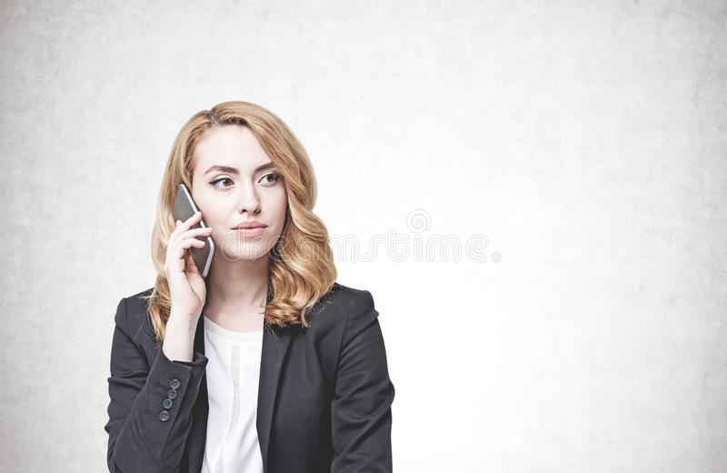 Mulher séria do gengibre no telefone, muro de cimento fotografia de stock royalty free