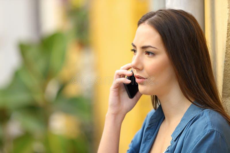 A mulher séria está falando no telefone na rua imagens de stock royalty free