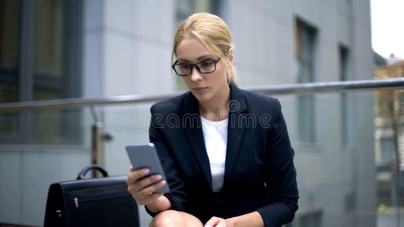 Mulher séria nos monóculos usando o telefone, problemas da visão devido ao excesso de trabalho imagens de stock royalty free