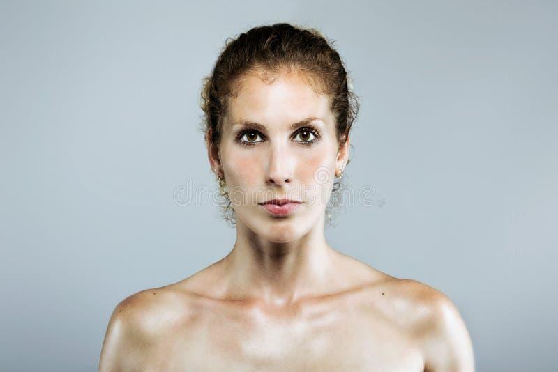 Mulher séria nova bonita que olha a câmera sobre o fundo cinzento foto de stock royalty free
