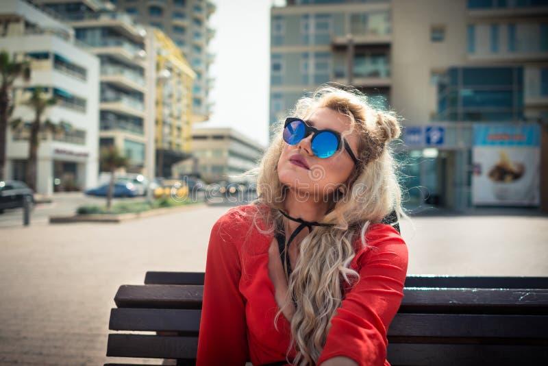 A mulher séria nova no vestido e em sunglass vermelhos elegantes senta-se sobre no banco imagem de stock