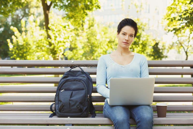 Mulher séria nova que usa o portátil no parque, espaço da cópia fotos de stock royalty free