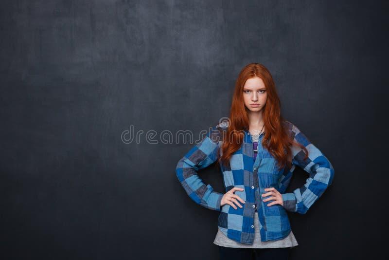 Mulher séria que está com mãos na cintura sobre o fundo do quadro-negro imagem de stock