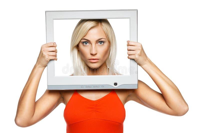 Mulher séria que olha através do frame do computador imagem de stock royalty free
