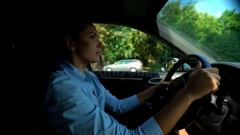 Mulher séria que procura o parque de estacionamento, motorista atento que mantém-se às regras da estrada fotografia de stock