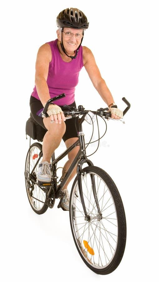 Mulher sênior apta de sorriso que monta uma bicicleta imagens de stock royalty free
