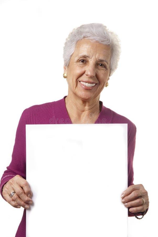 Mulher sênior atrativa que prende o quadro de avisos em branco imagem de stock royalty free