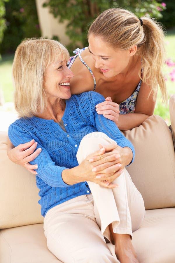 Mulher sênior com a filha adulta que relaxa em casa fotografia de stock royalty free