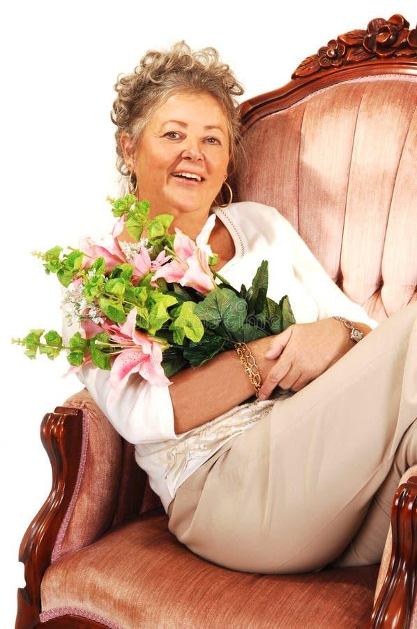 Mulher sênior com flores. fotografia de stock