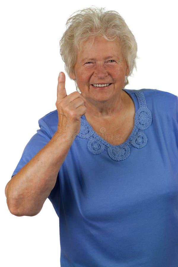 Mulher sênior com forefinger acima fotografia de stock
