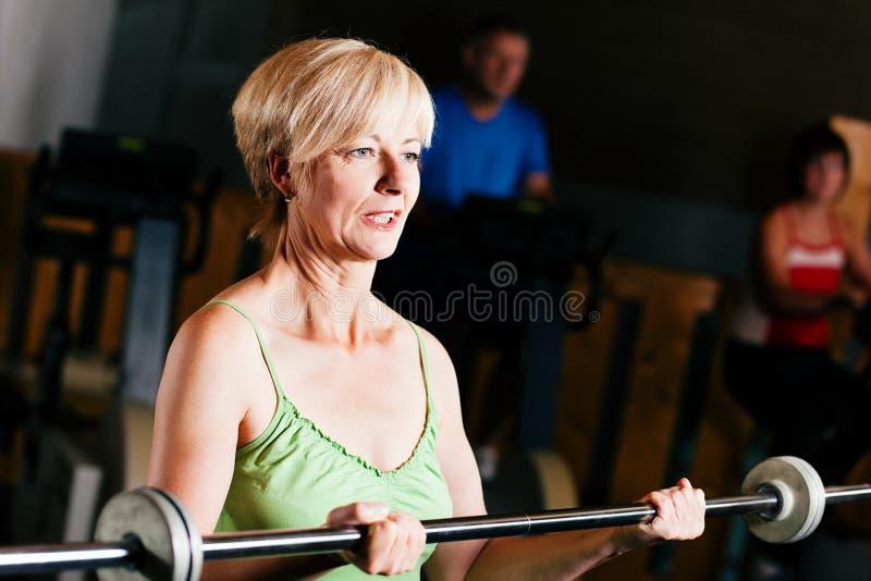 Mulher sênior com o barbell na ginástica fotografia de stock royalty free