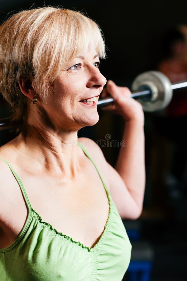 Mulher sênior com o barbell na ginástica imagens de stock royalty free
